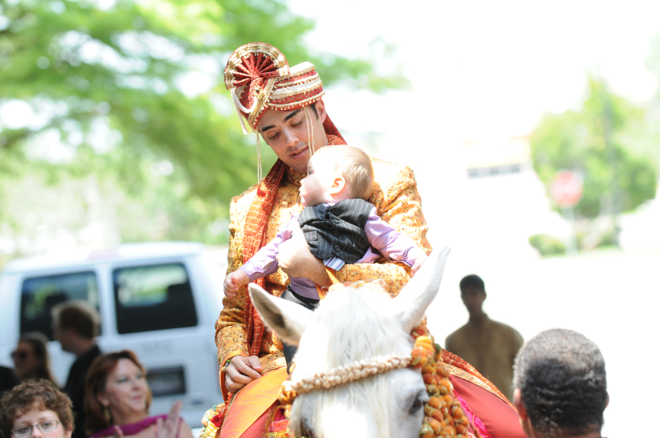 groom holding a baby